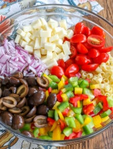 This Tangy Pasta Salad is filled with crunchy bell peppers and onions, tangy olives, and sweet tomatoes. Tossed in a light oil and vinegar dressing the recipe is great for summer parties.