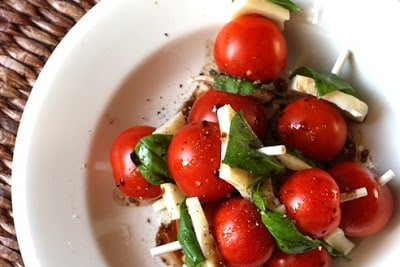 A bowl of food on a plate, with Tomato and Olive oil