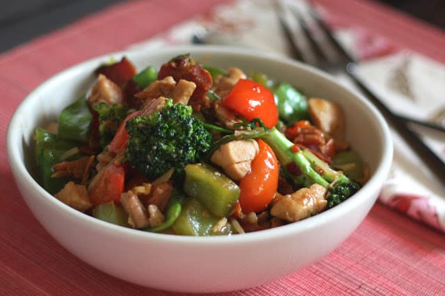 A bowl of food with broccoli, with Chicken and Kung Pao chicken