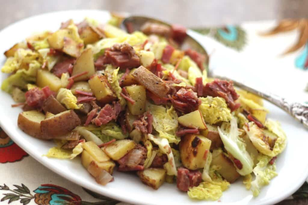 A plate of food, with Potato and Corned beef