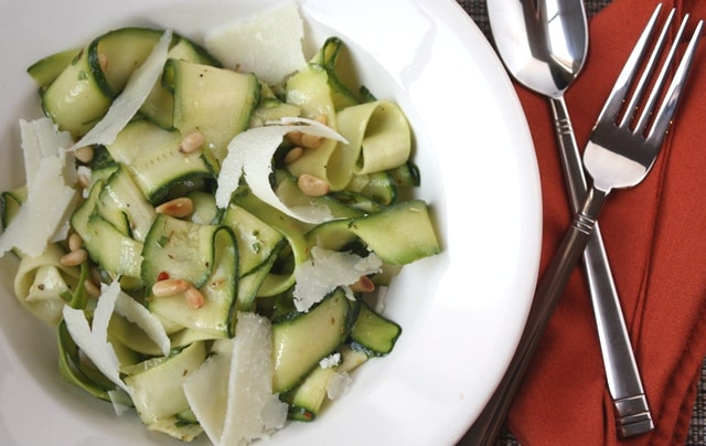 A bowl of salad and a fork on a plate, with Summer squash and Olive oil