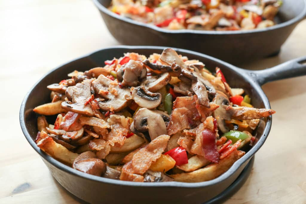 Montreal-Style Poutine piled high with Bacon, Peppers, Mushrooms, and Onions by Barefeet In The Kitchen