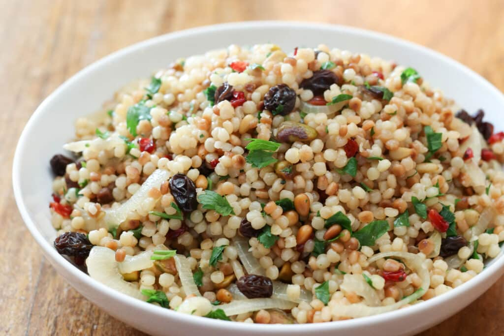 Israeli Coucous with pistachios, pine nuts, raisins, and more - the perfect recipe for a casual lunch or a fancy dinner.