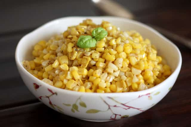 A bowl of rice on a plate, with Butter and Creamed corn