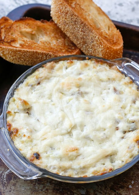 Rosemary Artichoke Dip is going be to your new party dip, appetizer, Friday night craving, and all around favorite hot snack! - Get the recipe at barefeetinthekitchen.com