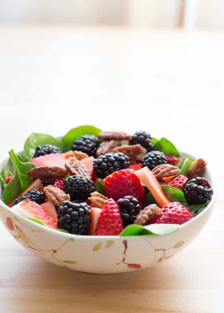 This Berry Pecan Salad is filled with fresh fruit, sugared almonds, and creamy poppyseed dressing, it's one of the season's best salads! Get the recipe at barefeetinthekitchen.com
