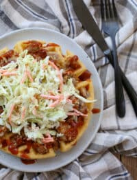 Cornbread Waffles topped with pulled pork and coleslaw on a plate. Get the recipe at barefeetinthekitchen.com